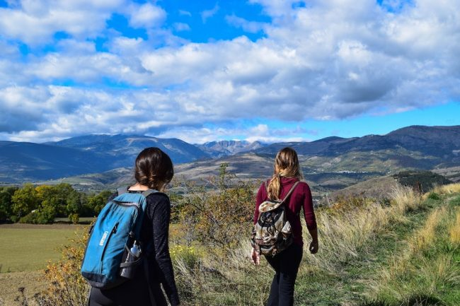 Two women hiking with mountains in the background