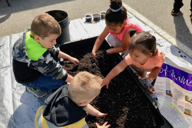 Kids around a sled of soil