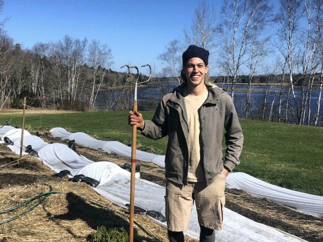 Gardener holding tool smiling at camera