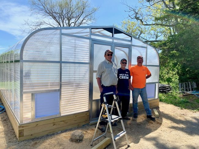 Three men standing in front of a recently constructed greenhouse